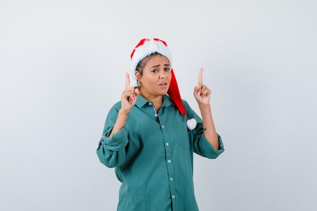 Jonge dame die omhoog wijst in kerstmuts, overhemd en er angstig uitziet. vooraanzicht.