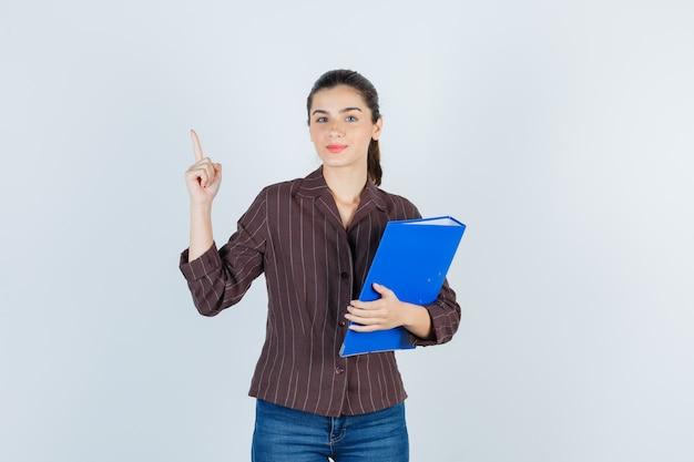 Jonge dame die omhoog wijst, map in shirt, spijkerbroek vasthoudt en er tevreden uitziet, vooraanzicht.