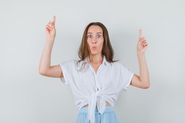 Jonge dame die omhoog wijst terwijl haar lippen in blouse en rok pruilen en geconcentreerd kijkt