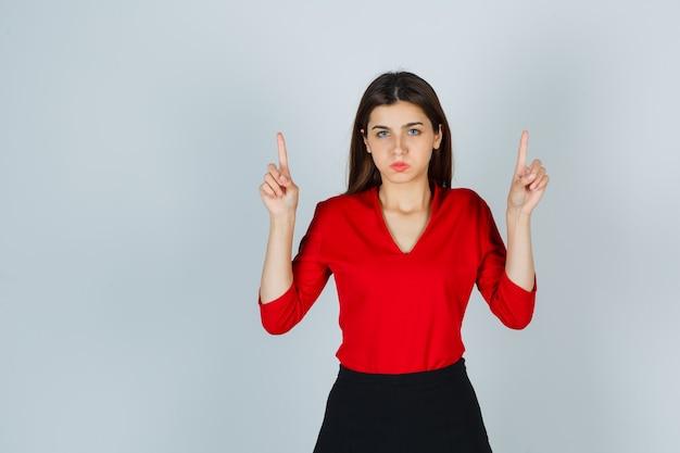 Jonge dame die omhoog wijst terwijl het blazen van wangen in rode blouse, rok en weemoedig kijkt