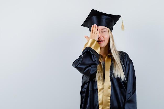Jonge dame die oog bedekt met hand in academische jurk en er schattig uitziet.