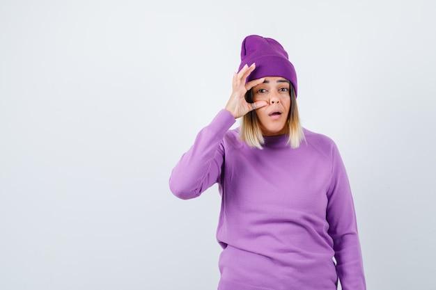 Jonge dame die oog opent met vinger in paarse trui, muts en perplex kijkt, vooraanzicht.