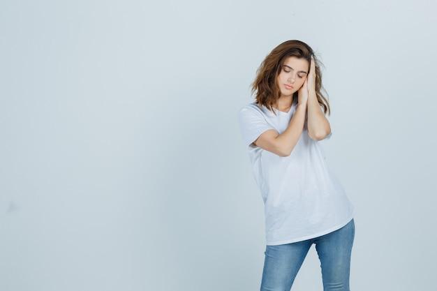Jonge dame die op handen als hoofdkussen in t-shirt, jeans leunt en slaperig kijkt. vooraanzicht.