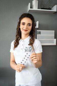Jonge dame die op medisch kostuum draagt en bij camera stelt. portret van glimlachende tandarts. de gelukkige hulpmiddelen van de artsenholding in handen.