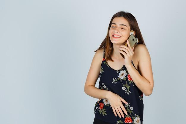 Jonge dame die op mobiele telefoon in blouse praat en er vrolijk uitziet, vooraanzicht.