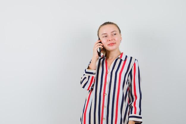 Jonge dame die op mobiele telefoon in gestreept overhemd spreekt en vrolijk kijkt