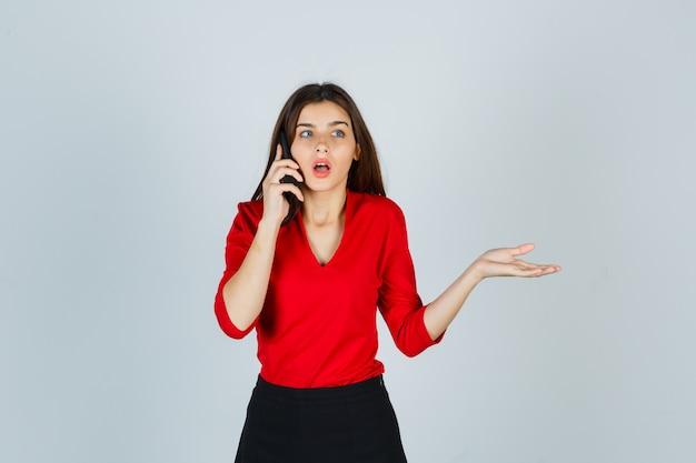 Jonge dame die op mobiele telefoon in rode blouse, rok spreekt en verbaasd kijkt