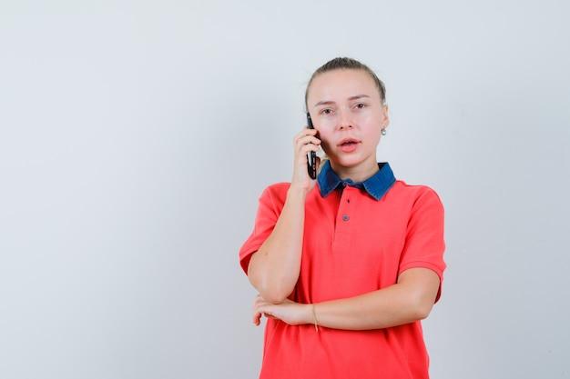 Jonge dame die op mobiele telefoon in t-shirt spreekt en peinzend kijkt