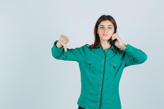 Jonge dame die op mobiele telefoon spreekt, duim in groen overhemd toont en ontevreden, vooraanzicht kijkt.