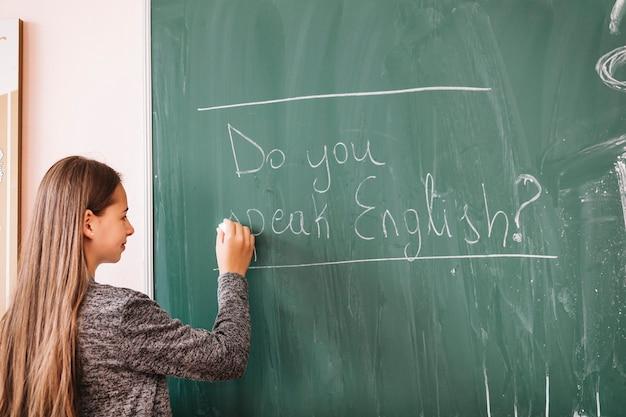 Jonge dame die op schoolbord schrijft