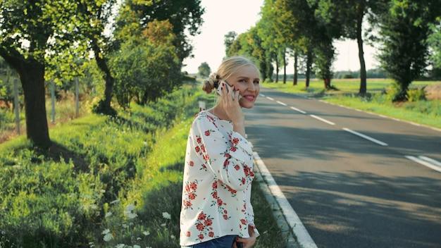 Jonge dame die op telefoon spreekt terwijl lift.
