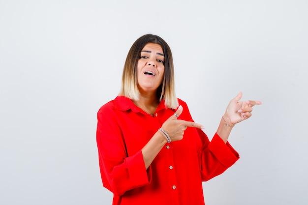 Jonge dame die opzij wijst in een rood oversized shirt en er opgewonden uitziet. vooraanzicht.