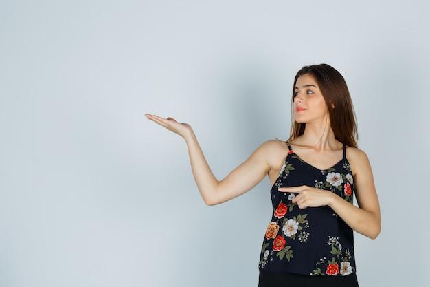 Jonge dame die opzij wijst terwijl ze een welkomstgebaar in een blouse doet en er zelfverzekerd uitziet. vooraanzicht.