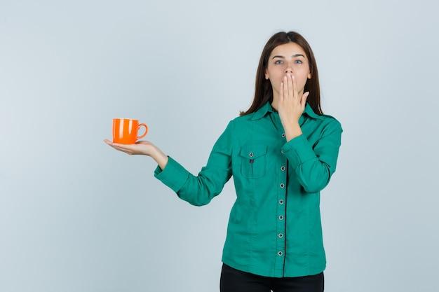 Jonge dame die oranje kop thee houdt, hand op mond houdt in overhemd en aantrekkelijk, vooraanzicht kijkt.