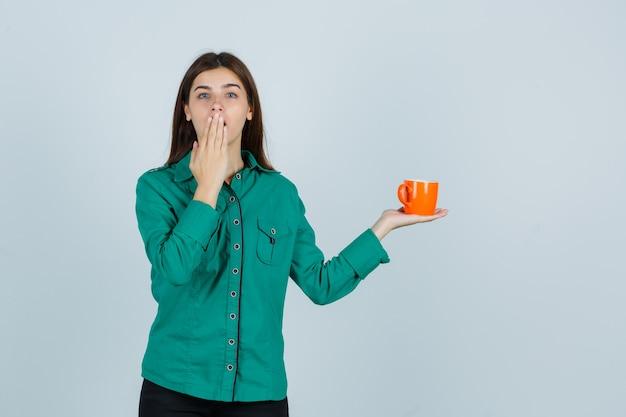 Jonge dame die oranje kopje thee houdt, hand op mond houdt in overhemd en gericht, vooraanzicht kijkt.