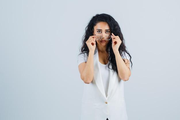 Jonge dame die over een bril in een wit t-shirt, een jas kijkt en er twijfelachtig uitziet. vooraanzicht.