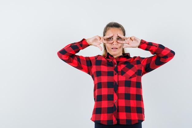 Jonge dame die overwinningsgebaar in geruit overhemd toont en zelfverzekerd kijkt