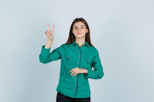 Jonge dame die overwinningsgebaar in groen overhemd toont en vrolijk, vooraanzicht kijkt.