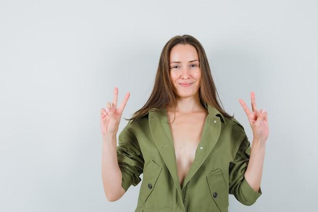Jonge dame die overwinningsgebaar in groene jas toont en zelfverzekerd kijkt