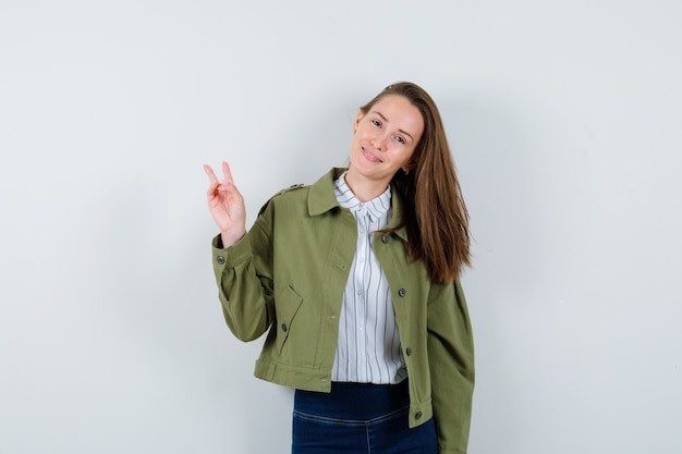 Jonge dame die overwinningsgebaar in overhemd, jasje toont en zelfverzekerd kijkt. vooraanzicht.