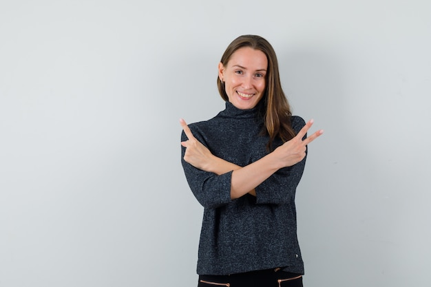 Jonge dame die overwinningsgebaar in overhemd toont en vrolijk kijkt