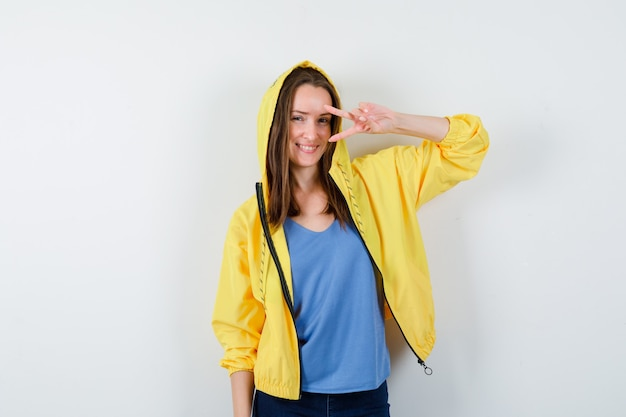 Jonge dame die overwinningsgebaar toont dichtbij oog in t-shirt, jasje en zelfverzekerd, vooraanzicht.