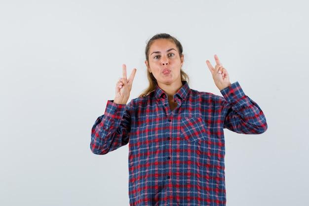 Jonge dame die overwinningsgebaar toont, tong uitsteekt in geruit overhemd en er zelfverzekerd uitziet. vooraanzicht.