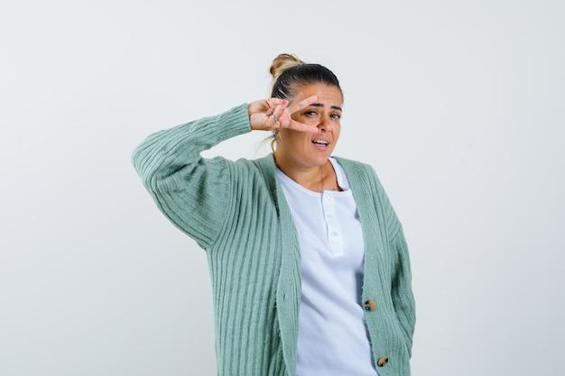 Jonge dame die overwinningsteken toont in t-shirt, jas en er gelukkig uitziet