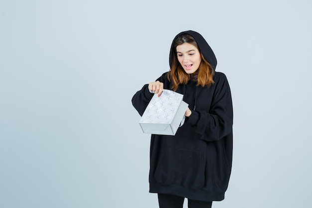 Jonge dame die pakket in oversized hoodie, broek onderzoekt en verbaasd kijkt. vooraanzicht.