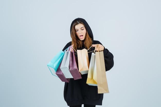 Jonge dame die pakketten in oversized hoodie, broek onderzoekt en verbaasd kijkt. vooraanzicht.