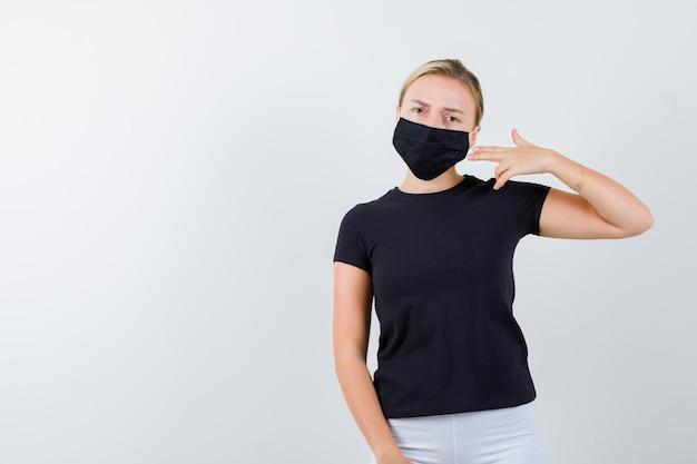 Jonge dame die pistoolgebaar toont in t-shirt, broek, medisch masker geïsoleerd