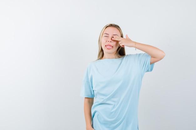 Jonge dame die pistoolgebaar toont terwijl tong in t-shirt uitsteekt en er schattig uitziet, vooraanzicht.