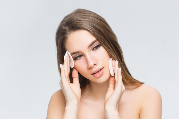 Jonge dame die poedervormige foundation op haar gezicht aanbrengt met cosmetische sponsrookwolk