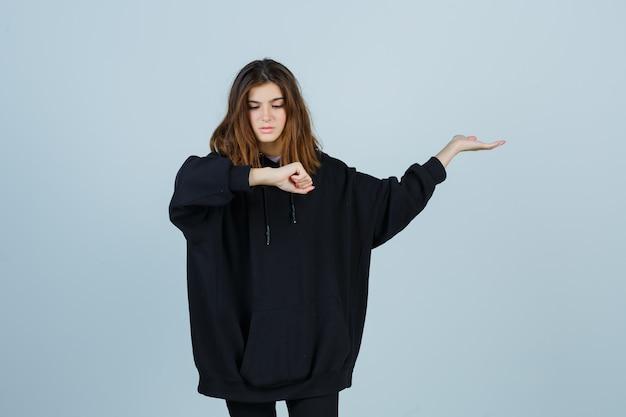 Jonge dame die pols bekijkt terwijl iets in oversized hoodie, broek wordt getoond en vergeetachtig kijkt. vooraanzicht.