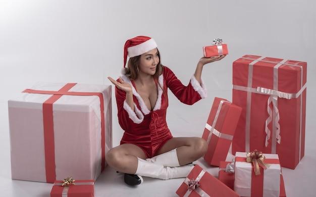 Jonge dame die rode jurk draagt, houdt geschenkdoos in de hand en kijkt met glimlach gezicht, gelukkig gevoel, model poseren