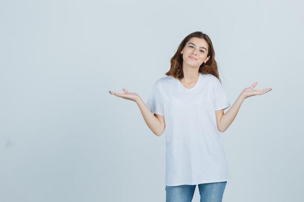 Jonge dame die schalengebaar in t-shirt, jeans toont en zelfverzekerd kijkt. vooraanzicht.