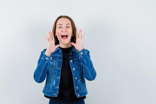 Jonge dame die schreeuwt of iets aankondigt in blouse, jas en er gelukkig uitziet, vooraanzicht.