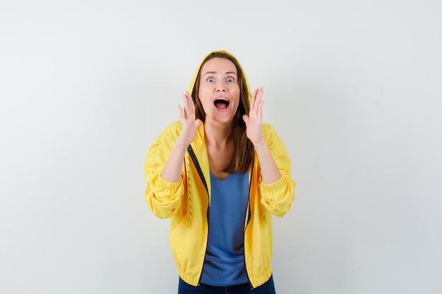 Jonge dame die schreeuwt of iets aankondigt in t-shirt, jas en er gelukzalig uitziet