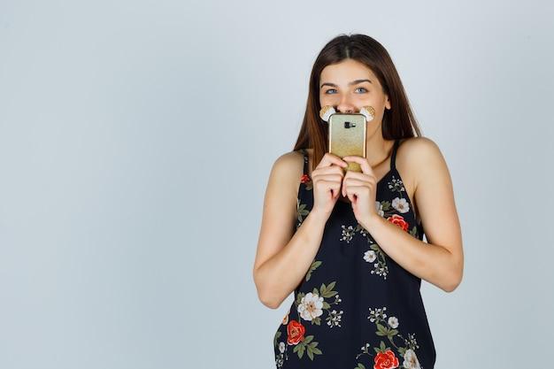 Jonge dame die smartphone in blouse houdt en beschaamd kijkt, vooraanzicht.