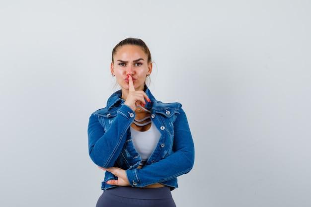 Jonge dame die stiltegebaar in bovenkant, spijkerjasje toont en ernstig kijkt. vooraanzicht.