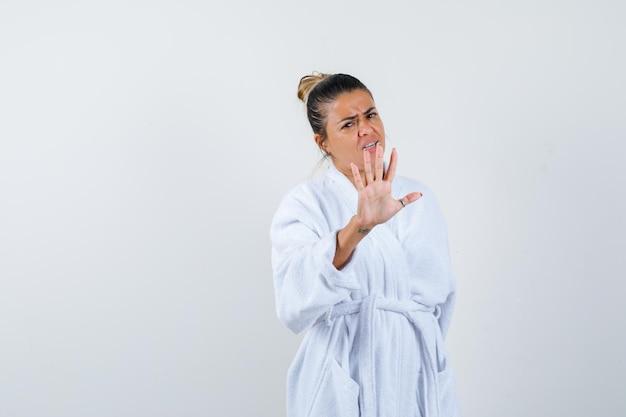 Jonge dame die stopgebaar in badjas toont en er bang uitziet Gratis Foto