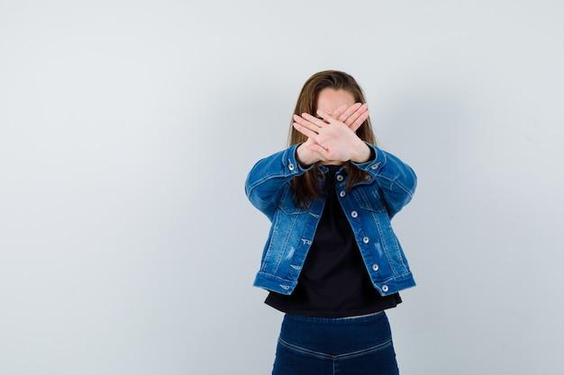 Jonge dame die stopgebaar in overhemd, jasje toont en resoluut kijkt. vooraanzicht.