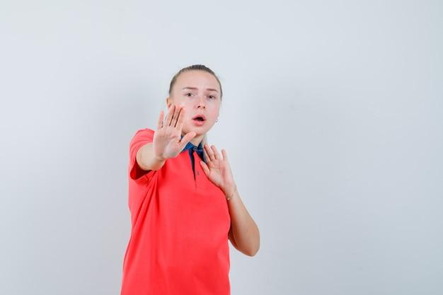 Jonge dame die stopgebaar in t-shirt toont en opgewonden kijkt