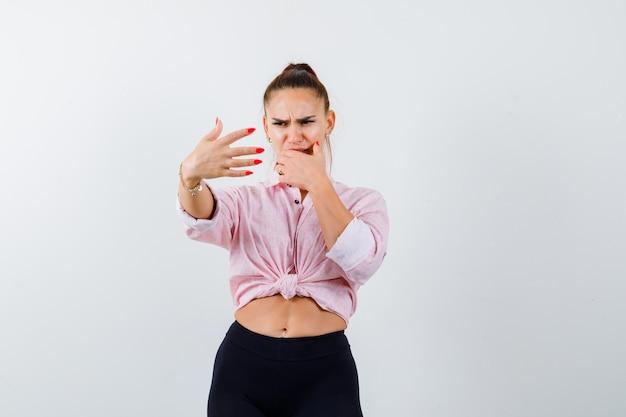Jonge dame die stopgebaar toont, hand op mond houdt in overhemd, broek en walgend kijkt