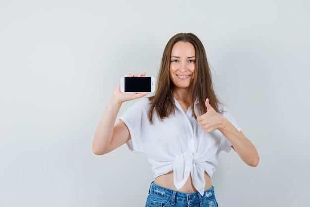 Jonge dame die telefoon toont terwijl duim in witte blouse wordt getoond en vrolijk, vooraanzicht kijkt.