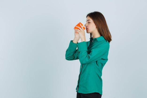 Jonge dame die thee drinkt uit oranje kop in overhemd en gericht, vooraanzicht kijkt.