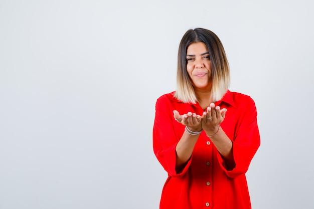 Jonge dame die tot een kom gevormde handen in een rood oversized shirt uitrekt en er tevreden uitziet, vooraanzicht.