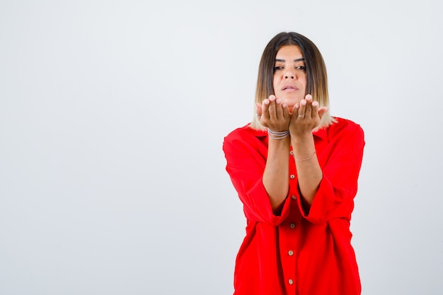 Jonge dame die tot een kom gevormde handen in een rood oversized shirt uitrekt en er zelfverzekerd uitziet, vooraanzicht.