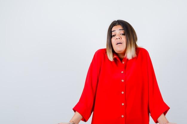 Jonge dame die twijfelgebaar in rood overmaats overhemd toont en perplex kijkt. vooraanzicht.
