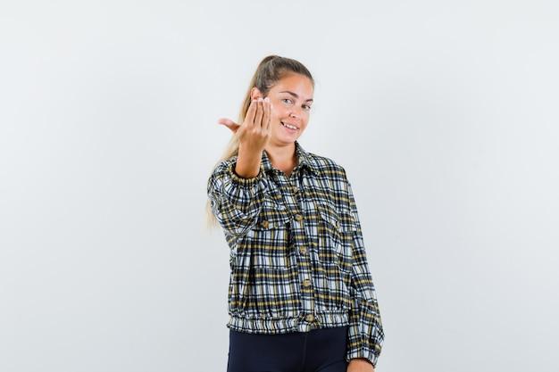 Jonge dame die uitnodigt om in shirt en korte broek te komen en er vrolijk uit te zien. vooraanzicht.
